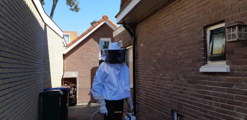 Een wespen bestrijder in zijn beschermende pak en masker