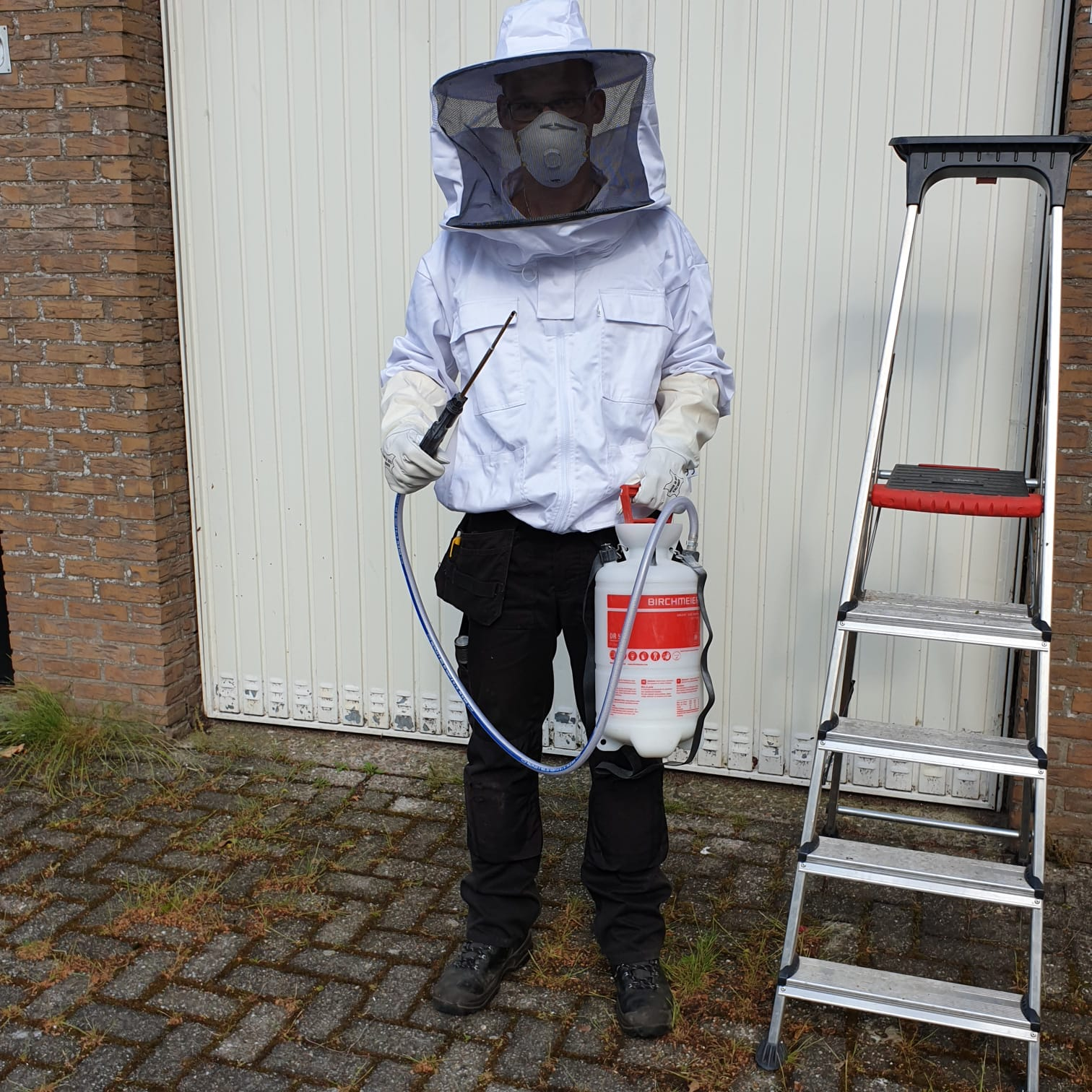 Wespen bestrijder in beschermende kleding